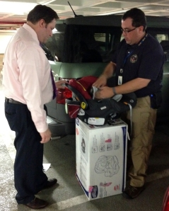 Photo of NTSB Investigator and CPS technician Dennis Collins demonstrating the process of properly installing a child safety seat.