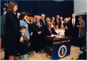 President Clinton signing the Aviation Disaster Family Assistance Act of 1996.