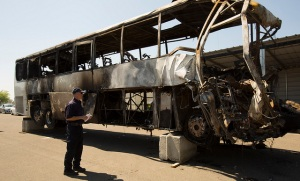 NTSB Investigator Robert Accetta documents the damage to the motorcoach.