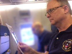 Picture of Member Robert Sumwalt reviewing the passanger safety briefing card before a commercial flight.